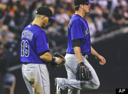 Colorado Rockies starting pitcher Drew Pomeranz flexes his right leg after being hit by a line drive from San Diego Padres batter Edinson Volquez during the second inning of a baseball game Monday, May 7, 2012 in San Diego. The Rockies' Marco Scutaro walks with Pomeranz. (AP Photo/Lenny Ignelzi)