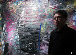 In this photo taken on Monday, April 2, 2012, Indonesian-Chinese farming tycoon Budi Tek poses in front of a painting by Gerhard Richter during an auction preview in Hong Kong. Tek is set to open the De Museum in Shanghai next year featuring Asian and Western contemporary art, after opening his first in Indonesia's capital Jakarta in 2008.