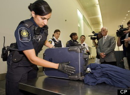 An airport security officer inspects a piece of luggage while media and Public Safety Minister Vic Toews, right centre, looks on during a demonstration of a typical secondary examination involving travellers arriving from abroad by the Canadian Boarder Services Agency at Pearson Airport in Toronto on Tuesday, August 9, 2011. (CP)