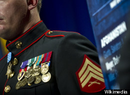 A U.S. Navy Medal of Honor recipient stands at attention while his award citation is read. (Wikimedia)