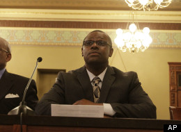 Illinois Rep. Derrick Smith, D-Chicago, listens to fellow lawmakers while attending a legislative committee hearing investigating whether Smith should be disciplined over a bribery charge at the Illinois State Capitol Thursday, May 10, 2012 in Springfield, Ill. Smith refused to answer the legislative panel's questions, but he insisted he is innocent. (AP Photo/Seth Perlman)