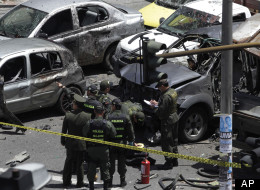 Police and firefighters work at the scene of a bomb in Bogota, Colombia, Tuesday, May 15, 2012. (AP Photo/Ricardo Mazalan)