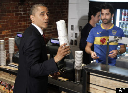 President Barack Obama holds up his hoagie sandwich that he purchased from David Mazza, right, co-owner of Taylor Gourmet during his visit to the local small business in the U Street neighborhood in Washington, Wednesday, May 16, 2012. Also behind the counter is Casey Patten, co-owner. (AP Photo/Pablo Martinez Monsivais)