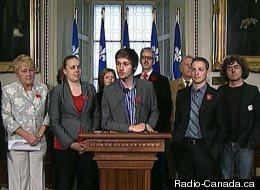 Léo Bureau-Blouin, au micro, accompagné par Martine Desjardins (à sa gauche), d'élus et de représentants des carrés verts et blancs. (Radio-Canada.ca)