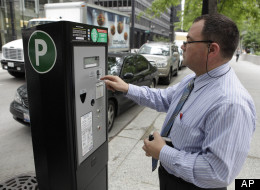 In this May 28, 2009 file photo, Sicilia Giovanni, of Chicago, feeds one of Chicago's new parking meters in Chicago. Chicago's parking meter deal was heavily criticized when it was approved in 2008. (AP Photo/Charles Rex Arbogast, File)