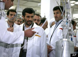 Iranian President Mahmoud Ahmadinejad (center) listens to a technician during a visit to the Natanz Uranium Enrichment Facility.