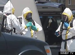 Officials in Hazmat suits clear the motel room of hazardous materials from the meth lab.