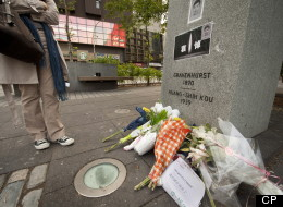 Concordia student Stephanie Chen stops for a moment where people have made a makeshift memorial for murder victim Jun Lin at the base of a monument to Norman Bethune in downtown Montreal on Monday, June 4, 2012. THE CANADIAN PRESS/Peter McCabe