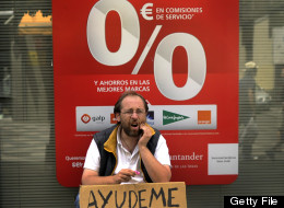 A man holding a cardboard reading ''help me'' asks for money in front of a bank in Madrid, on Juny 9, 2012. Spain has not changed its position and is not seeking aid for its banking sector, an economy ministry spokeswoman said on June 9 ahead of a conference call by eurozone finance ministers. (EDRO ARMESTRE/AFP/GettyImages)