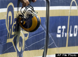 A fan holds a St. Louis Rams helmet along a barricade as they watch practice during NFL football training camp at the team's training facility Thursday, July 29, 2010, in St. Louis. (AP Photo/Jeff Roberson)