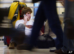 Matt Mason from Tampa, Fla., talks on his cell phone as he waits for a ride to his girlfiend's grandparents home in Franklin Park, Ill., at Midway Airport in Chicago, Wednesday, Nov. 23, 2005. (AP Photo/Charles Rex Arbogast)