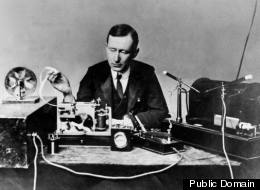 Guglielmo Marconi, the inventor of radio, sits with an early version of his transmitter and receiver.