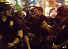 Police hold a skirmish line in downtown LA after a protest turned violent Thursday evening.
