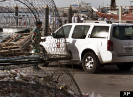 Emirati police and other officials inspect a boat docked in a fishing harbor in the Jumeirah district of Dubai, United Arab Emirates, Monday, July 16, 2012. (AP Photo/Almoutasim Almaskery)