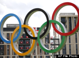 Swiss flag are seen through the Olympic rings at the Athletes' Village at the Olympic Park, Thursday, July 19, 2012, in London. (AP Photo/Jae C. Hong, Pool)