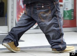 This May 8, 2009 photo shows a man holding up pants that are worn well below the waist, as he walks on a street in Nashville, Tenn. (AP Photo/Mark Humphrey)