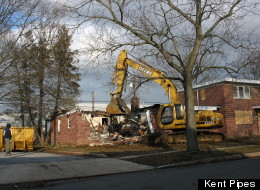 A bulldozer demolishes a home in Mount Holly Gardens, N.J.