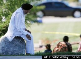 A man sits on a rock as police investigate the Sikh Temple of Wisconsin in Oak Creek, Wis., after a shooting Sunday, Aug 5, 2012. The intentions of the gunman, Wade Page, may forever elude authorities.