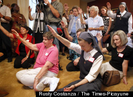 Attendees hold their hands up during a blessing by Archbishop Gregory Aymond, during the opening of the Magnificat House of Discernment for Women in New Orleans, Louisiana, Wednesday, August 15, 2012.