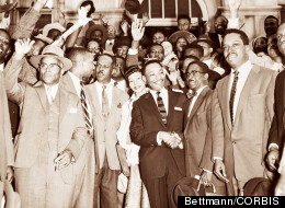 Rev. Martin Luther King, Jr., shaking hands with his lawyer, Arthur D. Shores, as they stand in front of cheering followers after King's conviction for his part in the bus boycott in Montgomery, 1956.