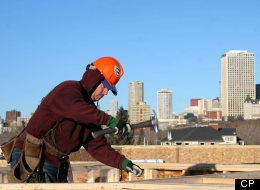 Framer Matthew Labossiere with Esquire Construction works on top of a condo development under construction on 98 Ave. in Edmonton overlooking the downtown skyline on Tuesday, March 3, 2007. Housing construction in Alberta is booming with the highest growth in the country. (Tim Smith)