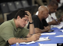 In this this Tuesday, Aug. 21, 2012, photo, job seekers fill out applications at a construction job fair in New York. (AP/Seth Wenig)