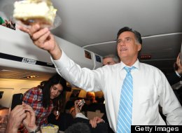 U.S. Republican presidential candidate Mitt Romney hands NBC producer Scott Foster a piece of cake as he celebrates his birthday aboard the Romney campaign plane en route to Boston on Sept. 14. (NICHOLAS KAMM/AFP/GettyImages)