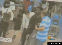 Lewis Jhon, in stripes, is shown in surveillance video detaining the shoplifting suspect.
