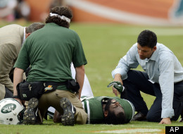 New York Jets trainers attend to cornerback Darrelle Revis during the second half of an NFL football game against the Miami Dolphins, Sunday, Sept. 23, 2012, in Miami.