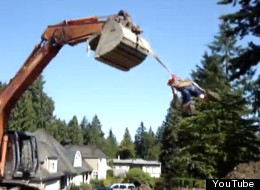 An excavator swings a B.C. man suspended from the bucket. (YouTube)