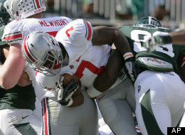 Ohio State's Jordan Hall (7) dives into the end zone for a touchdown against Michigan State's Shilique Calhoun, right, as Ohio State's Jack Mewhort, left, blocks during the first quarter of an NCAA college football game, Saturday, Sept. 29, 2012, in East Lansing, Mich.