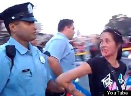 Aida Gusman is led away after allegedly being punched in the face by Philadelphia police Lt. Jonathan Josey.