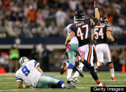 Tony Romo of the Dallas Cowboys lies on the turf as Chris Conte of the Chicago Bears celebrates a 74-yard interception return for a touchdown by Bears teammate Lance Briggs of the Chicago Bears in the third quarter at Cowboys Stadium on October 1, 2012 in Arlington, Texas.