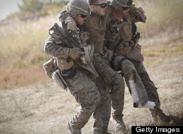 U.S. Marine lance corporal Zachary Densmor from 3rd Battalion, 7th Marines is carried by his comrades to a medevac helicopter after he was hit by an improvised explosive device (IED) in Helmand Province, Afghanistan on Oct. 31, 2011. (BEHROUZ MEHRI/AFP/Getty Images)