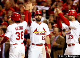 Matt Carpenter congratulates Pete Kozma and Daniel Descalso of the St. Louis Cardinals after both score on a RBI double by Jon Jay in the sixth inning against the San Francisco Giants in Game Four of the National League Championship Series at Busch Stadium on October 18, 2012 in St Louis, Missouri.