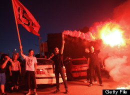 Members of the Greek extreme-right ultra nationalist party Golden Dawn (Chryssi Avghi), sing the National anthem out of the Golden Dawn's office in Thessaloniki on June 17, 2012.  (SAKIS MITROLIDIS/AFP/GettyImages)