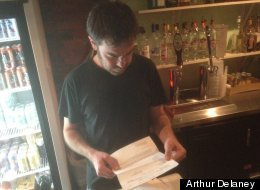 Washington bartender Mike Boone looks over one of the hospital bills he received after suffering multiple stab wounds fighting off a mugger.