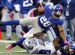 Dallas Cowboys wide receiver Dez Bryant (88) is taken down by New York Giants cornerback Jayron Hosley (28) and Stevie Brown (27) during the first half of an NFL football game Sunday, Oct. 28, 2012 in Arlington, Texas.