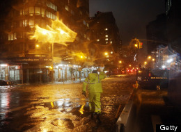 NEW YORK, NY - OCTOBER 29: A Con Edison worker walks through the flood waters on the corner of 33th Street and 1st Street in front of NYU Langone Medical Center in Manhattan during rains from Hurricane Sandy on October 29, 2012 in New York City. (Photo by Michael Heiman/Getty Images)