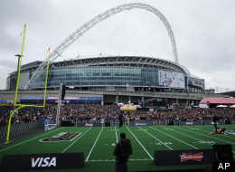 The crowd gathers prior to a NFL football game between St Louis Rams and the New England Patriots at Wembley Stadium, seen in background, in London, Sunday, Oct. 28, 2012.