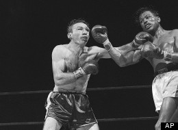 Weary and limp from their long battle, Carmen Basilio an Sugar Ray Robinson trade blows in closing minutes of their 15-round title fight at Yankee Stadium, New York City, September 23, 1957. Basilio, a deep cut over his left eye and groggy from the long ring stint, won a split decision and the middleweight title from Robinson.