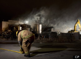 An emergency worker rolls up a hose outside Neptune Technologies and Bio Resources in Sherbrooke, Que., Thursday, November 8, 2012 where a large explosion at the plant sent a number of people to hospital with serious injuries. THE CANADIAN PRESS/Graham Hughes.