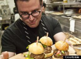 Le chef invité Danny St-Pierre tient les mini burgers de ragoût de boulettes et pattes de cochon