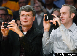 Thorsten Heins, left, CEO of Research in Motion, and Andrew Bocking, senior vice president, Software Product Management at Research In Motion, take a picture with their mobile devices during the Los Angeles Lakers and Phoenix Suns NBA basketball game at Staples Center on November 16, 2012 in Los Angeles, California. (Photo by Kevork Djansezian/Getty Images)