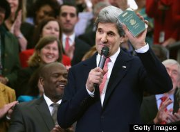 U.S. Secretary of State John Kerry holds up his first diplomatic passport he received as an 11-year-old boy while making remarks to employees on his first day at the State Department February 4, 2013 in Washington, DC. Kerry was issued the passport when he traveled with his father, a foreign service diplomat, to post-WWII Germany. (Photo by Chip Somodevilla/Getty Images)