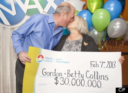 Gordon and Betty Collins of Placentia, N.L., kiss as they display their $30-million LOTTO MAX top prize cheque from the Jan. 25, 2013 draw in St.John's, N.L. on Thursday, Feb.7, 2013. THE CANADIAN PRESS/Graham Kennedy